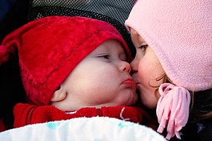 A young girl kisses a baby on the cheek.
