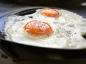 Eggs, sunny-side up, frying in a pan.