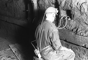 A miner listens to the movement of the mine.