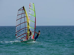 The windsurfer in the foreground is using a ca...