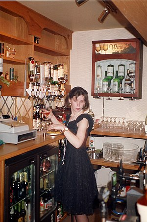 A student working as a barmaid in a British pub.
