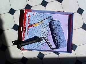 paint roller beside paint brush at paint reservoir