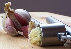 An Ikea garlic press, with pressed garlic.