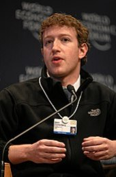 """Waist high portrait of man in his twenties, looking into the camera and gesturing with both hands, wearing a black pullover shirt that says """"The North Face"""" and wearing identification on a white band hanging from his neck"""