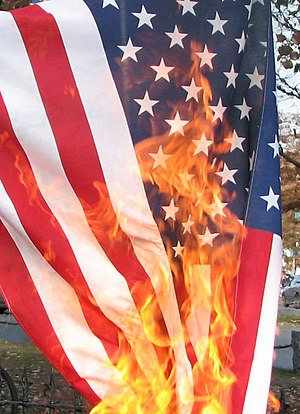 United States flag being burnt in protest, in ...
