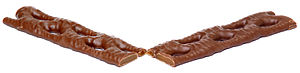 A Cadbury Curly Wurly candy bar, shown split i...