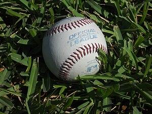 English: A baseball on grass.