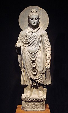 standing Buddha statue with draped garmet and halo
