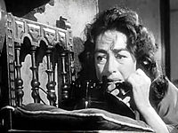 Facial shot of a dishevelled Crawford in bed, on the telephone.
