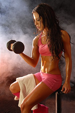 Fitness Model posing with dumbell. Photo by Gl...