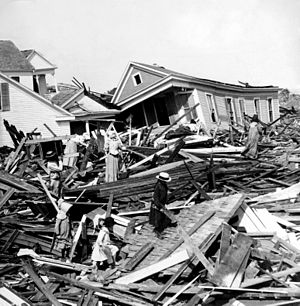 People rummage through rubble of destroyed hou...