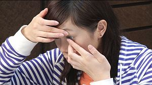 English: Putting on contact lenses