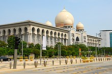 Building taken from a view of the corner. Beige colour, surrounded by columns. A large dome can be seen on the roof, surrounded by 3 others