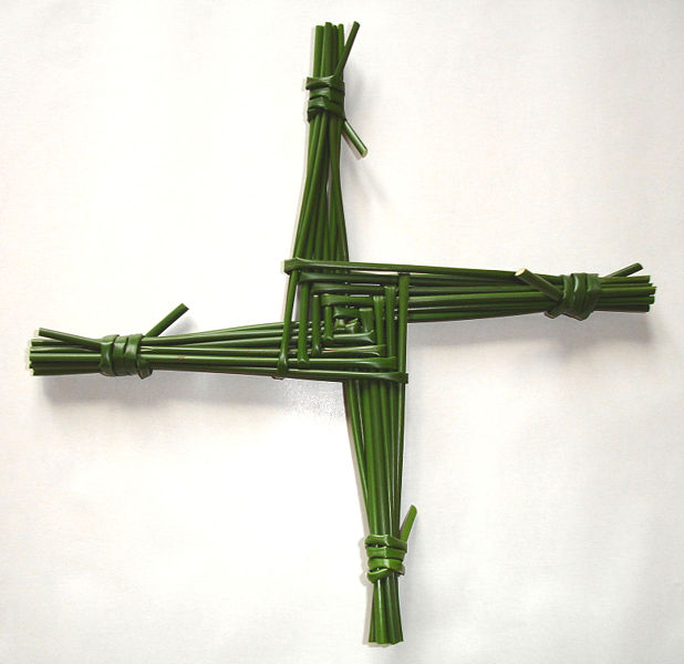 a green cross, woven out of straws, on a white background