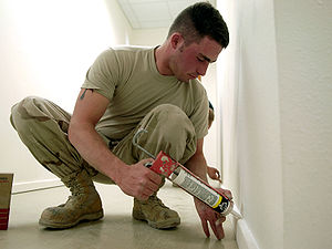 Man putting caulk on baseboard