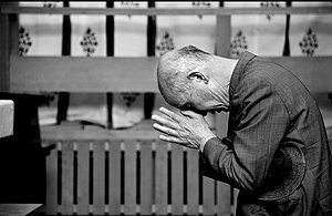 A Japanese man bowing in prayer at the Kamakur...