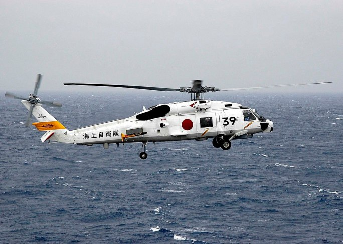 US Navy 060322-N-7981E-015 A Japan Maritime Self Defense Force SH-60J helicopter carrying Commander Destroyer Squadron Nine (CDS-9), Capt. Jeff Harley, departs the flight deck of the Nimitz-class aircraft carrier USS Abraham L