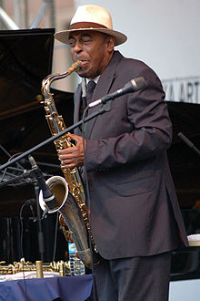 Archie Shepp on stage in a suit playing saxophone