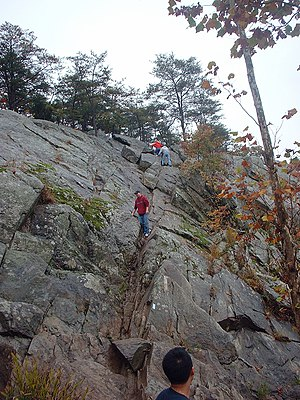 Students scaling a steep cliff face on Section...