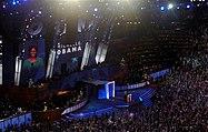 Michelle Obama Spreekt op Een conventie;  Haar imago en de naam van Worden geprojecteerd op Een Groot Scherm achter Haar.  Het Grote Publiek Golven verticale blauwe borden.