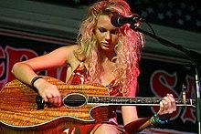 Taylor Swift zit en leunt dan Haar eiken gitaar while Het oppakken Een reeks