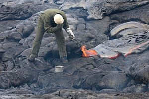 English: A geologist collecting a lava sample ...