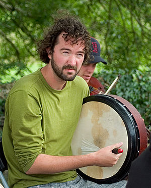 A man playing a bodhrán, an Irish frame drum. ...