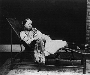 Woman with bound feet reclining on chaise loun...