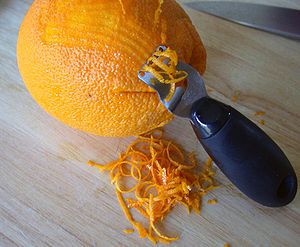 Using an orange zester to zest an orange.