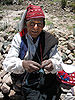 English: Man of Taquile knitting. He is also w...