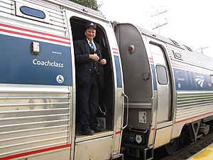 English: Amtrak Downeaster conductor standing ...