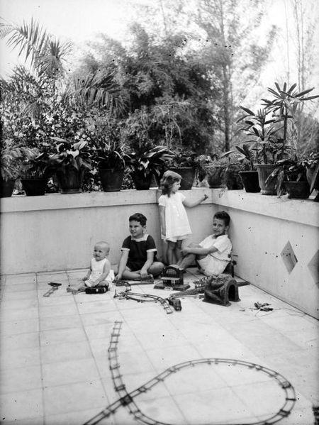 450px COLLECTIE TROPENMUSEUM Europese kinderen en een baby met een modelspoorbaan op de galerij van een woonhuis TMnr 10023898 Mainan Bocah Belanda VS Mainan Bocah Pribumi