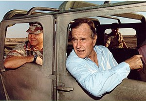 (George H.W. Bush riding in a Humvee with Gene...