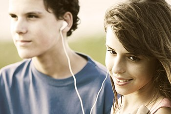 Teens sharing earphones, listening music outdo...