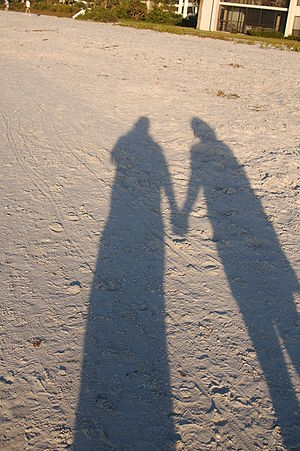 Holding Hands shadow on sand