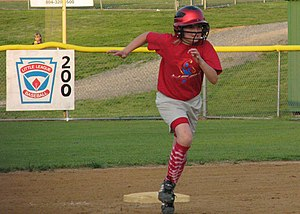 Softball player rounding second base after a hit.