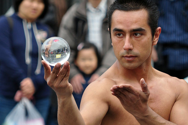 Image of street performer looking at a crystal ball