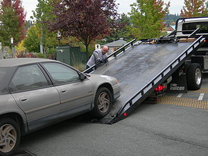 English: A car being loaded onto a flatbed tow...