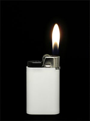 A white lighter showing a flame against a blac...
