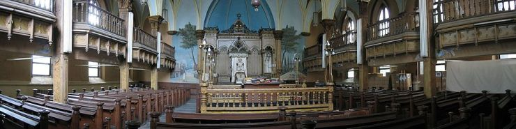 A wide, panoramic view of a synagogue sanctuary can be seen. Three rows of wooden pews lead to the front of the room; the middle row is interrupted by a raised square wooden platform, surrounded by a heavy wooden railing with lights on each corner. At the front of the room is a large wooden ark, surrounded on three sides by painted scenes of buildings and trees. At the sides of the room are balconies with heavy wooden railings, interrupted by large columns.