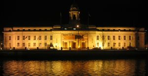 Cork City Hall is illuminated at night, reflec...