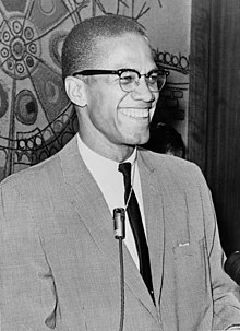 A 38-year-old man in a suit and tie is grinning. He wears glasses and has a microphone around his neck
