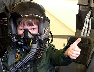 Young military brat gives thumbs up while wear...