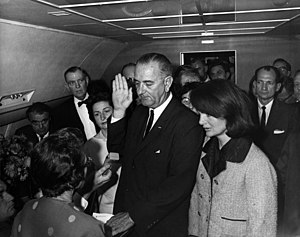 Lyndon B. Johnson being sworn in aboard Air Force One by Federal Judge Sarah T. Hughes, following the assassination of John F. Kennedy. To the right of Johnson (from the viewer's point of view) is Jacqueline Kennedy, widow of Kennedy; to his right (our left) is Mrs. Lady Bird Johnson.