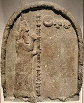 Stone stele with a carving depicting a man with a beard, carrying a tall staff and wearing a robe and conical hat, gesturing to three symbols representing the moon, sun and Venus.