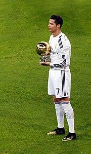 Un homme en chemise blanche pose avec un ballon en or alors qu'il se tient debout sur un terrain de football.