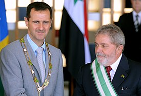 "Bashar al-Assad wearing the ""Grand Collar"" of the National Order of the Southern Cross, accompanied by Brazilian President Luiz Inácio Lula da Silva in Brasília, 30 June 2010"
