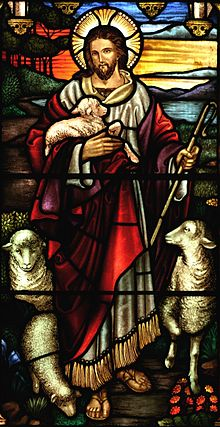 A stained glass depiction of Jesus as a Caucasian man with long brown hair, a beard and the characteristic Christian cross inscribed in the halo behind his head. The figure dressed in a white inner robe cover by a shorter, looser scarlet robe. Depicted as a Shepard, he is holding a crux in his left hand and carrying a lamb in his right. Sheep are positioned to the left and right of the figure.