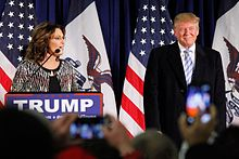 "Donald Trump with former Alaska governor Sarah Palin in January 2016. Palin is standing on the left side of the image, behind a podium with a sign that has the word ""TRUMP"" in white-on-blue text. Trump is standing on the right side of the image. There are American flags hanging on poles behind them and the outlines of an audience in front of them."