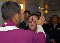 A priest marks a cross of ashes on a worshipper's forehead.